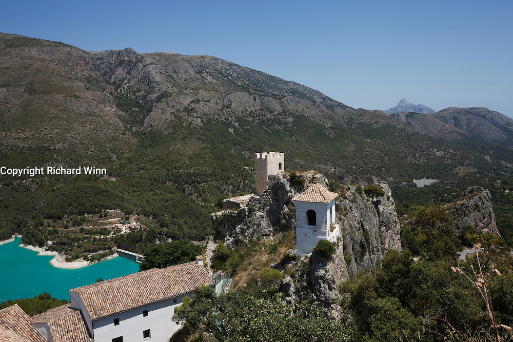 View of the bell tower, the reservoir on the Guadalest river and the mountain ranges beyond, from the top of Castell d'Alcozaiba, in the village of Guadalest, in the Alicante region of Spain.