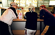 Three young men ordering food at a fast food counter.