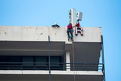 "© Licensed to London News Pictures; 11/06/2020; Bristol, UK. Contractors remove the letters ""Colston Tower"" from the Colston Tower office block in the city centre, following renewed controversy over the name of 17th century slave trader and Bristol philanthropist Edward Colston. At a Black Lives Matter protest the previous Sunday the statue of slave trader Edward Colston which has stood in Bristol city centre for over 100 years was pulled down with ropes and thrown in Bristol Docks by protesters during the BLM rally and march through the city centre in memory of George Floyd, a black man who was killed on May 25, 2020 in Minneapolis in the US by a white police officer kneeling on his neck for nearly 9 minutes. Edward Colston (1636 – 1721) was a wealthy Bristol-born English merchant involved in the slave trade, a Member of Parliament and a philanthropist. He supported and endowed schools, almshouses, hospitals and churches in Bristol, London and elsewhere, and his name is commemorated in several Bristol landmarks, streets, three schools and the Colston bun. The killing of George Floyd has seen widespread protests in the US, the UK and other countries. Photo credit: Simon Chapman/LNP."