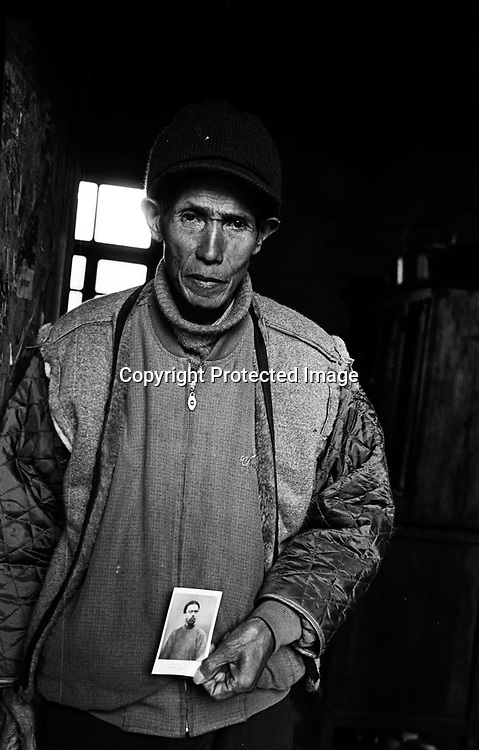 """CIZHONG, DECEMBER 17, 2000: Bernard, 75, holds a picture of Maurice Tournay, one of the French missionaries who built the Catholic church in Cizhong at then end of the 19th century, Yunnan province , December 17, 2000. Bernard went to jail for 22 years after the foreign missionaries left Cizhong in 1952 for having assisted them . he passed away in 2003..The church in Cizhong is believed to be the real life model for James Hilton's famous novel """" lost Horizon""""- a description of Shangri-La-..Maurice Tournay also happens to be one of the catholic martyrs who were canonized by pope Paul II on October 1, 2000.."""