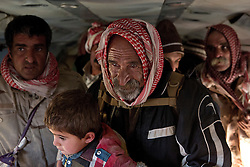 © Licensed to London News Pictures. 11/12/2014. Fishkhabour, Iraq. An elderly Yazidi refugee holds a young relative as he waits for his chance to leave an Iraqi Air Force Mi-17 Hip helicopter and be processed by members of the UNHCR after being evacuated from Mount Sinjar.<br /> <br /> Although a well publicised exodus of Yazidi refugees took place from Mount Sinjar in August 2014 many still remain on top of the 75 km long ridge-line, with estimates varying from 2000-8000 people, after a corridor kept open by Syrian-Kurdish YPG fighters collapsed during an Islamic State offensive. The mountain is now surrounded on all sides with winter closing in, the only chance of escape or supply being by Iraqi Air Force helicopters. Photo credit: Matt Cetti-Roberts/LNP