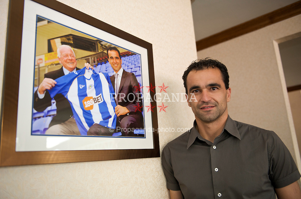 WIGAN, ENGLAND - Monday, August 24, 2009: Wigan Athletic's manager Roberto Martinez stands in front of a photograph of himself with Wigan chairman Dave Whelan after returning to the club as a manager. (Photo by David Rawcliffe/Propaganda)