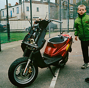 Little boy in a green jacket standing next to a red scooter