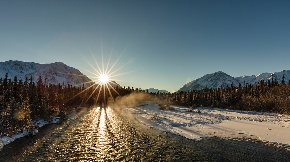 Rising mist over the Kathleen River is illuminated by the low winter sun in Kluane National Park in the Yukon Territory. Afternoon.