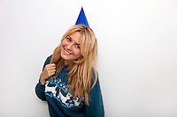Portrait of cheerful woman wearing party hat against white background
