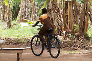 A school girl rides home on one of the bicycles that have been provided by Cadburys at the Mbaem community school, Ghana.