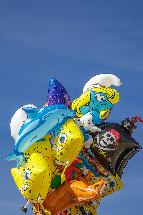 A bunch of helium filled balloons at Oktoberfest in Munich, Germany. The balloons are of cartooon characters and are multicoloured.