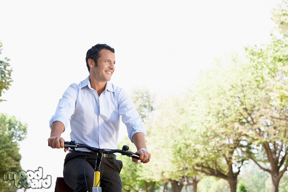 Businessman riding bicycle in park low angle