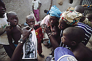 Soumana Natomo's two wives and a number of their children in the community of Kouakourou, Mali, look at photographs from the initial countries shot for Material World: A Global Family Project before they decided to paticipate in the project. Mali was the third country photographed. The Natomo family lives in two mud brick houses in the village of Kouakourou, Mali, on the banks of the Niger River. They are grain traders and own a mango orchard. According to tradition Soumana is allowed to take up to four wives; he has two. Wives Pama and Fatoumata are partners in the family and care for their many children together.