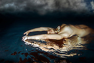 A surreal of a girl swiming nude just below the water surface.  The image is reversed so she appears to be swimming on her back just above the water's surface, with a dark cloudy sky above her.