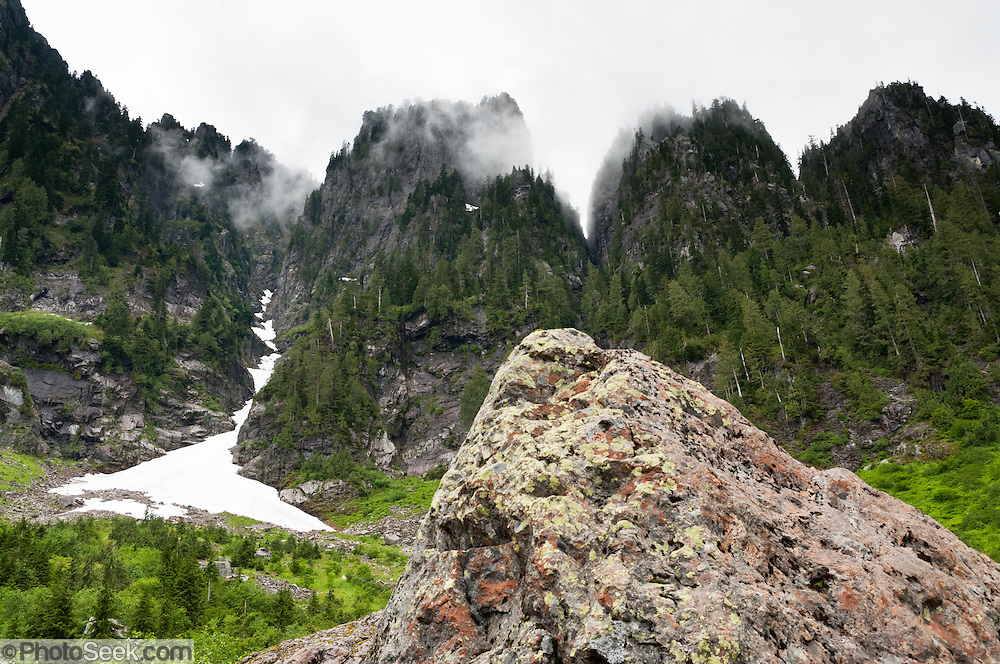 A ridge in Mount Pilchuck Natural Resources Conservation Area rises above lichen covered rocks at Lake 22, a trail near Verlot on the Mountain Loop Highway, Snohomish County, Washington, USA.