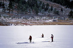 Stock photo of three men ice fishing on a frozen lake