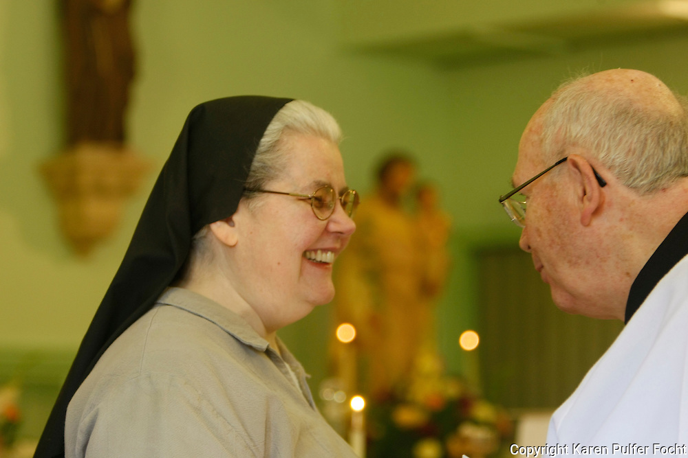 Sister Margarite, a cloistered Poor Clare Nun from Memphis, Tennessee. The number of Poor Clare nuns in Memphis is dwindling. They are a community of Catholic women who have chosen to embrace the way of life proposed by a young Italian girl in Assisi over 800 years ago. Father James Pugh (rt)