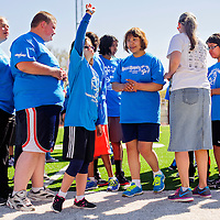 050314       Cable Hoover<br /> <br /> Special Olympics athlete Sarah Tempest, center, waves at her family while lining up with her fellow competitors during the Special Olympics track meet at Public School Stadium in Gallup Saturday.