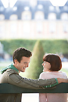 Young couple sitting on bench looking over shoulder in park