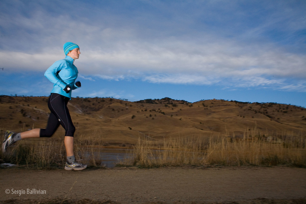 A woman is running outdoors while she trains for a marathon in Boulder, Colorado