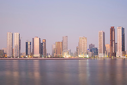Dusk skyline view of beach and modern high-rise apartment buildings along Corniche in Sharjah United Arab Emirates