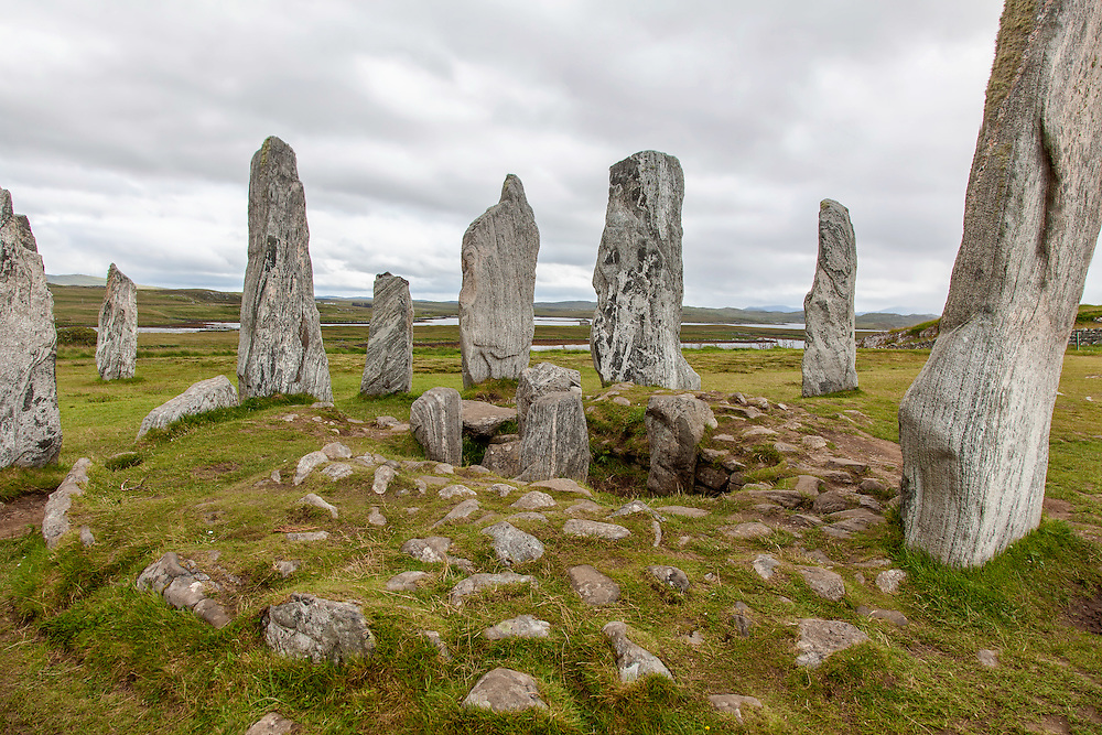 The Callanish Stones (Clachan Chalanais or Tursachan Chalanais in Gaelic) are an arrangement of standing stones placed in a cruciform pattern with a central stone circle. They were erected in the late Neolithic era, and were a focus for ritual activity during the Bronze Age. They are near the village of Callanish (Calanais) on the on the North East edge of The Isle of Lewis in the Outer Hebrides, Scotland.<br /> <br /> This photograph is a colour version of the view of the Callanish Standing Stones on the Isle of Lewis. The photograph can be purchased as print, mounted print in frames, canvas or aluminum or as a digital file.