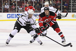 Oct 13; Newark, NJ, USA; Los Angeles Kings defenseman Alec Martinez (27) plays the puck while being defended by New Jersey Devils right wing David Clarkson (23) during the second period at the Prudential Center.