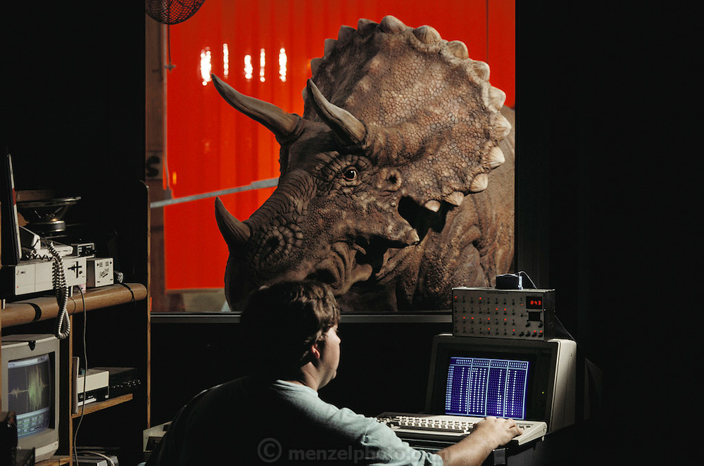 Eric Hvinden puts sound onto a Dinamation International Triceratops at the company's factory near Los Angeles, California. Dinamation International, a California-based company, makes a collection of robotic dinosaurs. The dinosaurs are sent out in traveling displays to museums around the world. The dinosaur's robotic metal skeleton is covered by rigid fiberglass plates, over which is laid a flexible skin of urethane foam. The plates and skin are sculpted and painted to make the dinosaurs appear as realistic as possible. The creature's joints are operated by compressed air and the movements controlled by computer.