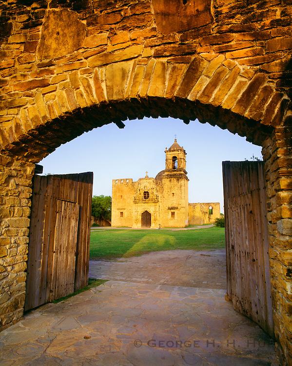 0506-1021C ~ Copyright:  George H. H. Huey ~ Church of San Jose y San Miguel de Aguayo, at sunset, through mission wall doors.  Church construction began 1720.  San Antonio Missions National Historical Park, Texas.