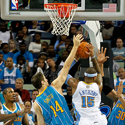 October 29, 2010; New Orleans, LA, USA; Denver Nuggets small forward Carmelo Anthony (15) is defended by New Orleans Hornets power forward Jason Smith (14) and power forward David West (30) during the third quarter at the New Orleans Arena.  Mandatory Credit: Derick E. Hingle