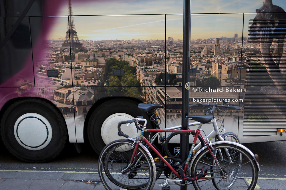 A passing tour bus featuring the city of Paris, france and locked up bikes, on 17th January 2018 in Westminster, London, England.