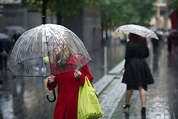 © Licensed to London News Pictures. 01/10/2012. London, UK.  A woman sheltering from heavy rain underneath an umbrella in Central London on October 1st, 2012. Photo credit : Ben Cawthra/LNP