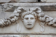 Mask and garland frieze from the Portico of Tiberius on the Southern portico of the Agora, 1st century AD, Aphrodisias, Aydin, Turkey. The Sculpture School at Aphrodisias was an important producer of carved marble sarcophagi and friezes from the 1st century BC until the 6th century AD. The Portico of Tiberius was built under the reign of Tiberius and has many examples of mask and garland friezes, consisting of the heads of gods, goddesses, theatrical characters, mythological figures or masks, each with a distinct facial expression, between hanging garlands of leaves, fruit and flowers. This example may represent surprise. Aphrodisias was a small ancient Greek city in Caria near the modern-day town of Geyre. It was named after Aphrodite, the Greek goddess of love, who had here her unique cult image, the Aphrodite of Aphrodisias. The city suffered major earthquakes in the 4th and 7th centuries which destroyed most of the ancient structures. Picture by Manuel Cohen