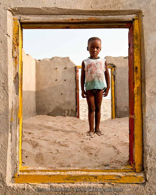 Seven year-old Collins Kusietey in the remains of a house destroyed by the encroaching sea in Totope, Ghana on 7 March 2010. According to locals, this was a habitable dwelling as little as three years ago.