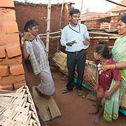 CAPTION: Jyothi has multiple disabilities, including cerebral palsy. Her parents are in the process of constructing a new home, so Mobility India representative Ramesh has come to advise them on the modifications they will need to build in so as to make the house as accessibe to her as possible. He suggests wall bars and foot steps (moulds in the floor) to help her get around the house, and also a specially adapted toilet. LOCATION: Yangahalli (village), Haradanahalli (hobli), Chamrajnagar (district), Karnataka (state), India. INDIVIDUAL(S) PHOTOGRAPHED: From left to right: Doreswamy, Ramesh, Jyothi and Lakshmamma.