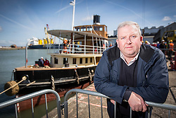 "© Licensed to London News Pictures. 04/05/2016. Birkenhead UK. Picture shows Dan Cross who bought the Daniel Adamson in 2004 for £1 from the Manchester Canal Ship Company. The Daniel Adamson steam boat has been bought back to operational service after a £5M restoration. The coal fired steam tug is the last surviving steam powered tug built on the Mersey and is believed to be the oldest operational Mersey built ship in the world. The ""Danny"" (originally named the Ralph Brocklebank) was built at Camel Laird ship yard in Birkenhead & launched in 1903. She worked the canal's & carried passengers across the Mersey & during WW1 had a stint working for the Royal Navy in Liverpool. The ""Danny"" was refitted in the 30's in an art deco style. Withdrawn from service in 1984 by 2014 she was due for scrapping until Mersey tug skipper Dan Cross bought her for £1 and the campaign to save her was underway. Photo credit: Andrew McCaren/LNP ** More information available here http://tinyurl.com/jsucxaq **"