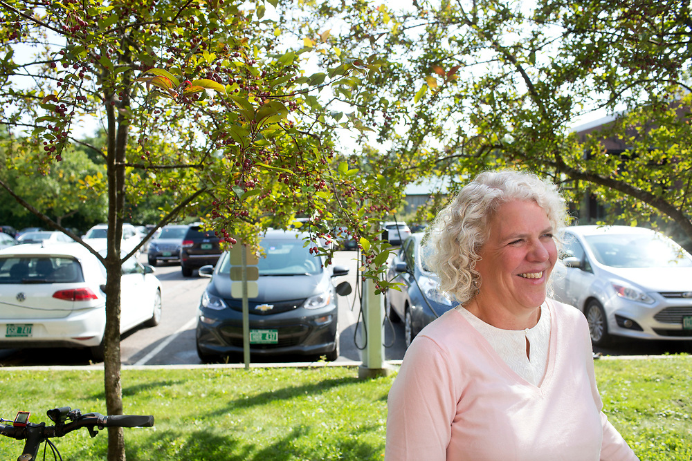 """Photographed at an electric vehicle charging station outside her Burlington, Vt., office on Sept. 11, 2017, Jennifer Wallace-Brodeur is the director of transportation efficiency at the Vermont Energy Investment Corporation. """"Vermont has spent a lot of time over the last many years really focused on energy in the building sector and getting results,"""" she said. """"We now need a real focus on transportation systems."""" (Photo by Geoff Hansen)"""