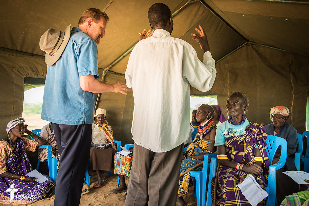 The Rev. Robert Pase, pastor of Grace Lutheran Church, Midland, Texas, and Faith Lutheran Church, Andrews, Texas, evangelizes alongside a local member of Lutheran Hour Ministries during a LCMS Mercy Medical Team clinic on Monday, June 20, 2016, in Nataparkakono, a village in Turkana, Kenya.  LCMS Communications/Erik M. Lunsford