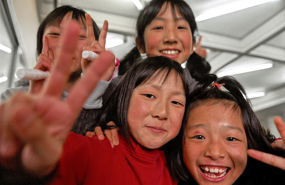 Japan, Toyama-ken, Ohyama. January/18/2005...A group of Gr.4 elementary girls smile and salute the camera with the peace sign during morning recess break.