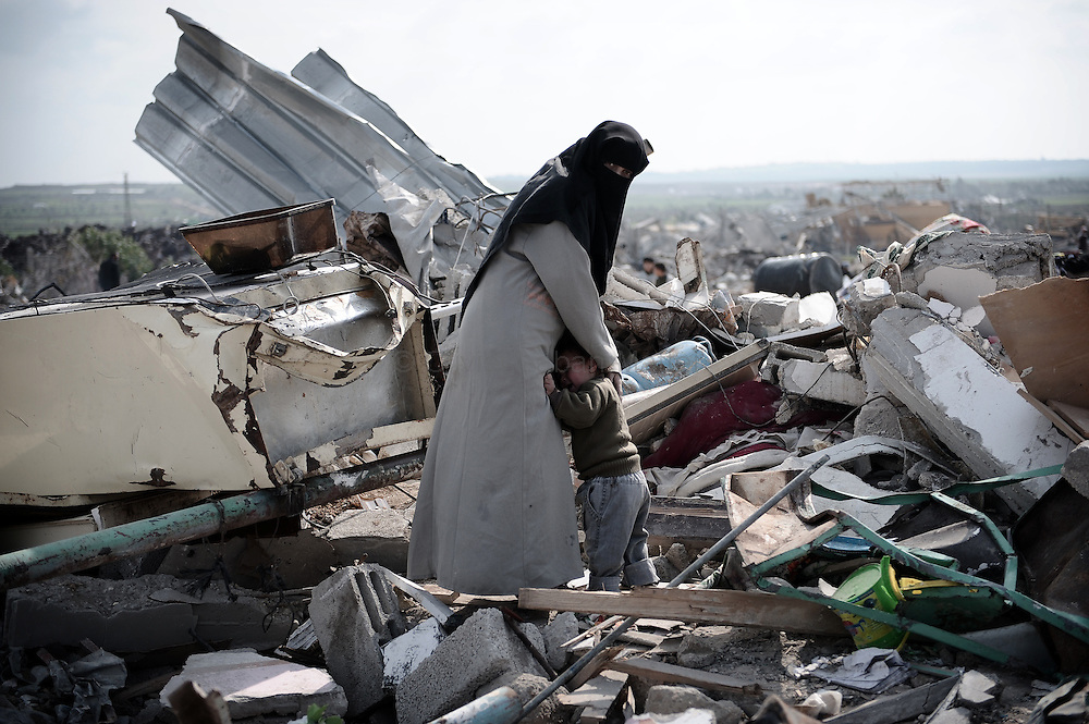 A Palestinian woman comforts her child on the rubble of her house, on January 19, 2009, in Jabalia's Ezbet Abdrabbo neighborhood. A tenuous ceasefire held in Gaza, where Palestinians dug out from the rubble and Hamas put on a show of defiance vowing to fight on after the Jewish state's deadliest war on the strip.
