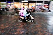 In Utrecht rijdt een stelletje op een scooter door de regen.<br /> <br /> In Utrecht a couple is riding on a scooter in the rain.