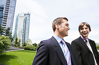 Two business men laughing near office buildings