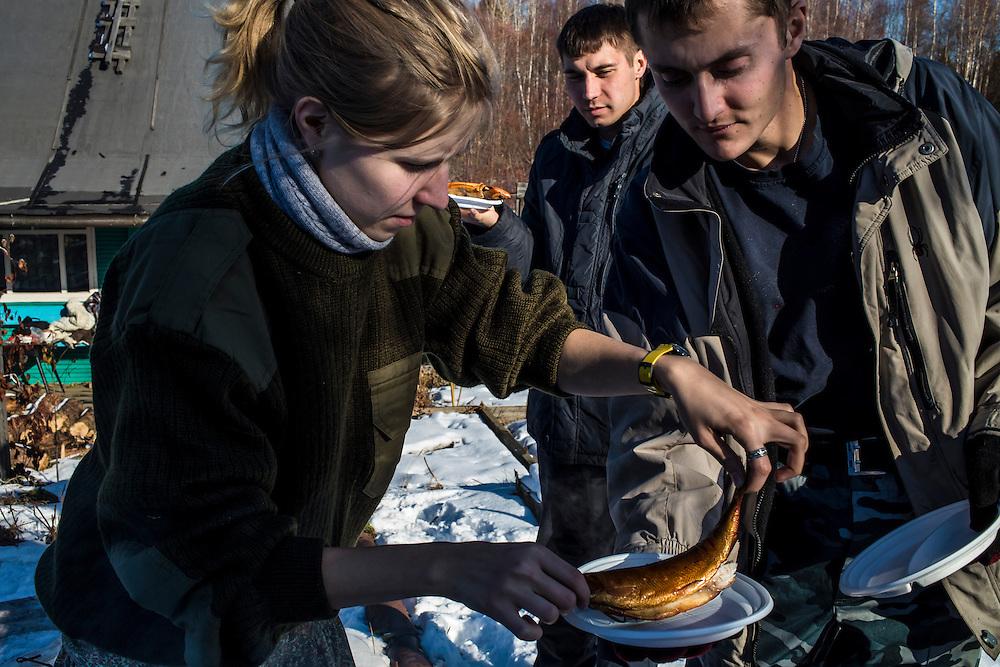 Marina Telezhnikova, Maxim Makarov, and Vadim Kovalenko, from left, smoke Omul, a type of fish found in Lake Baikal, at Vadim's dacha on Sunday, October 27, 2013 in Baikalsk, Russia.