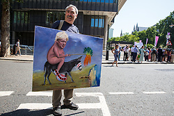 London, UK. 23 July, 2019. Political artist Kaya Mar displays his painting depicting Boris Johnson in front of campaigners for a People's Vote protesting outside the Queen Elizabeth II Centre prior to the announcement inside the venue that Boris Johnson had been elected as leader of the Conservative Party and would replace Theresa May as Prime Minister.