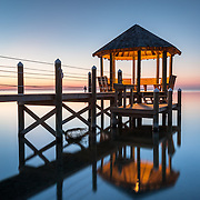 The blue hour of evening settles over a calm Pamlico Sound in Hatteras, North Carolina.  Part of a private rental residence, this coastal gazebo is situated near a popular marina and boating channel.  Hatteras Island is one of several barrier island towns off the coast of North Carolina in the greater area known as the Outer Banks (OBX).