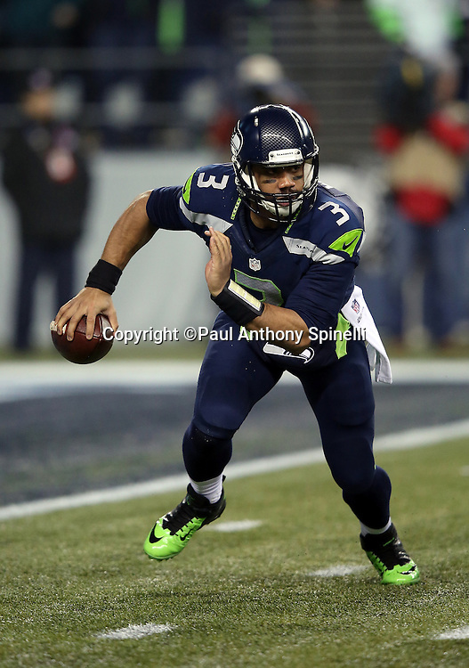 Seattle Seahawks quarterback Russell Wilson (3) scrambles and runs the ball for a 14 yard gain and a third quarter first down during the NFL week 19 NFC Divisional Playoff football game against the Carolina Panthers on Saturday, Jan. 10, 2015 in Seattle. The Seahawks won the game 31-17. ©Paul Anthony Spinelli