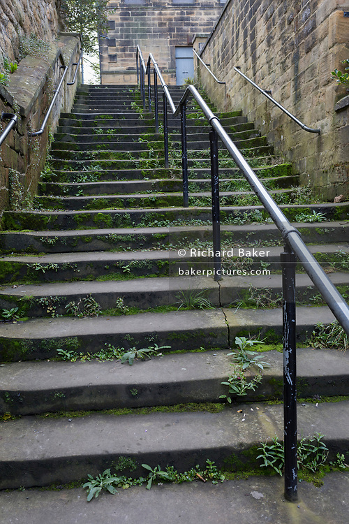 Worn stone steps rise uphill in a Northumbrian town side street, on 26th September 2017, in Alnwick, Northumberland, England.