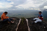 La Gran Sabana, Venezuela, 14-04-2011. Cargadores indigenas descansan al borde del Roraima tepuy en La Gran Sabana.  Localizada al sur de Venezuela en el macizo Guayanés en la parte sureste del Estado Bolívar hasta la frontera con Brasil. En ella conviven diversos grupos indígenas, entre ellos la etnia Pemón. La Gran Sabana forma parte de uno de los Parques Nacionales más extensos de Venezuela, el Parque Nacional Canaima. La Gran Sabana, 14 Abril  de 2011. .(Ramon Lepage / Orinoquiaphoto/ LatinContent/Getty Images)..Trail to Kukenam and Roraima tepui. Tepuis are large mesas that rise out of dense jungle in southeast Venezuela and adjacent Brazil and Guyana. Over 100 of these plateaus rise above the verdant landscape of this region, which is known in Venezuela as the Gran Sabana and also the Guyana Highlands. Tepuis are comprised of Precambrian sandstone, and are some of the oldest exposed rock formations in the world. Monte Roraima is one of the best known of the tepuis and has a labyrinth of rock forms and endemic plants on its summit..