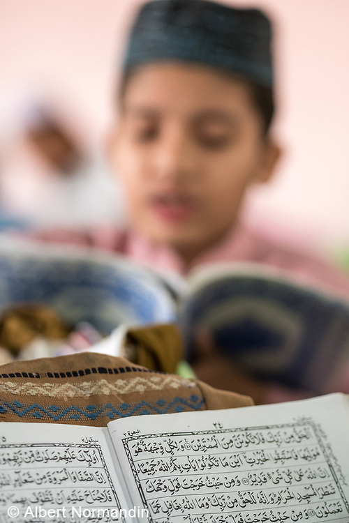 Muslim School student reads book out of focus, Mawlamyine, Myanmar