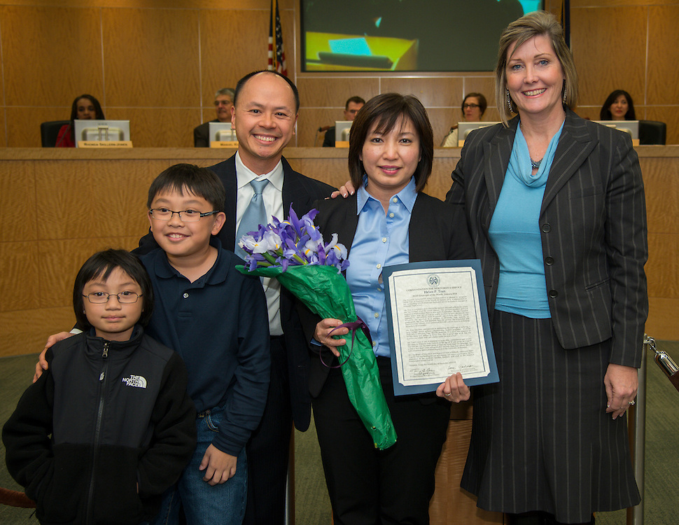 Westside High School principal Marguerite Stewart, right, and Employee of the Month Helen Tran, center, pose for a photograph with the Tran family during a Houston ISD Board of Education meeting, December 12, 2013.