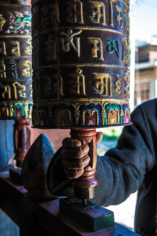 A passer by turns a prayer wheel in Bhumtang, Bhutan