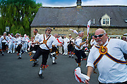 Morris dancers, Brighton Morris Men, perform a dancing display at The Kings Head Pub in Bledington, Oxfordshire, UK