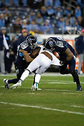 Jacksonville Jaguars running back Leonard Fournette (27) has his jersey pulled as he is gang tackled by Tennessee Titans inside linebacker Wesley Woodyard (59) and Tennessee Titans outside linebacker Derrick Morgan (91) during the week 14 regular season NFL football game against the Tennessee Titans on Thursday, Dec. 6, 2018 in Nashville, Tenn. The Titans won the game 30-9. (©Paul Anthony Spinelli)