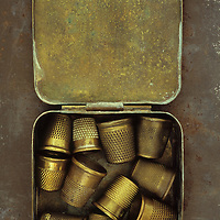 Collection of old brass thimbles in a tin container